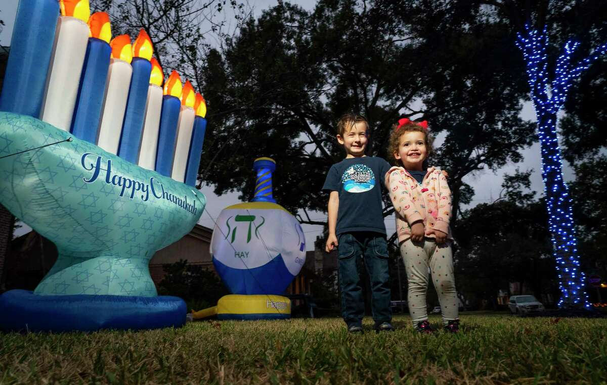 Max, 6, and Charlotte, 2, Davis excitedly tend to yard decorations. Their family is participating in a driving tour of decorated homes called the Chanukah Hop Houston.