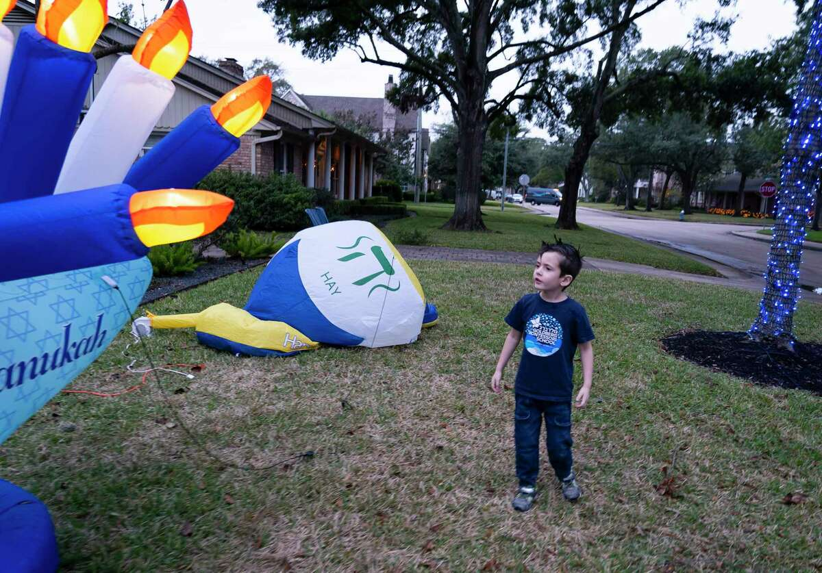 Six-year-old Max Davis watches an inflatable menorah fill with air as the sun goes down Wednesday, Dec. 2, 2020, in Houston. The family put up Hanukkah decorations in their front yard for the first time this year. They are participating in a driving tour of decorated homes called the Chanukah Hop Houston.