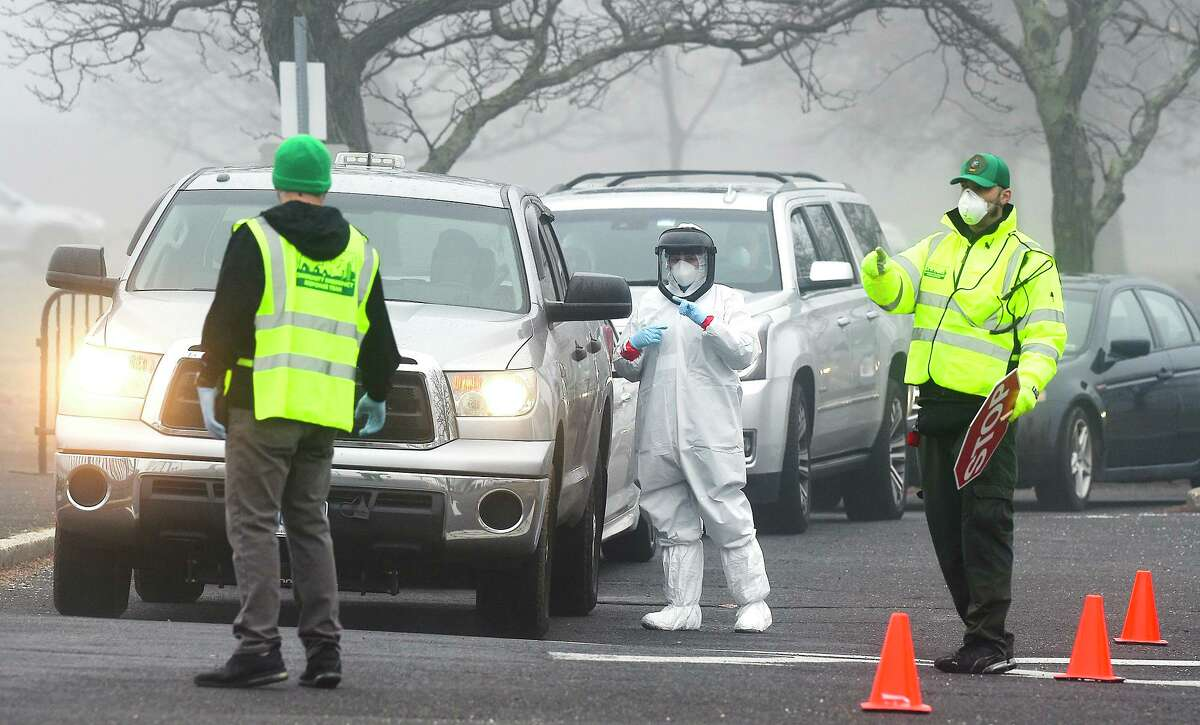 A line of cars wait at a coronavirus mobile testing site set up at Cummings Beach in Stamford on March 20.