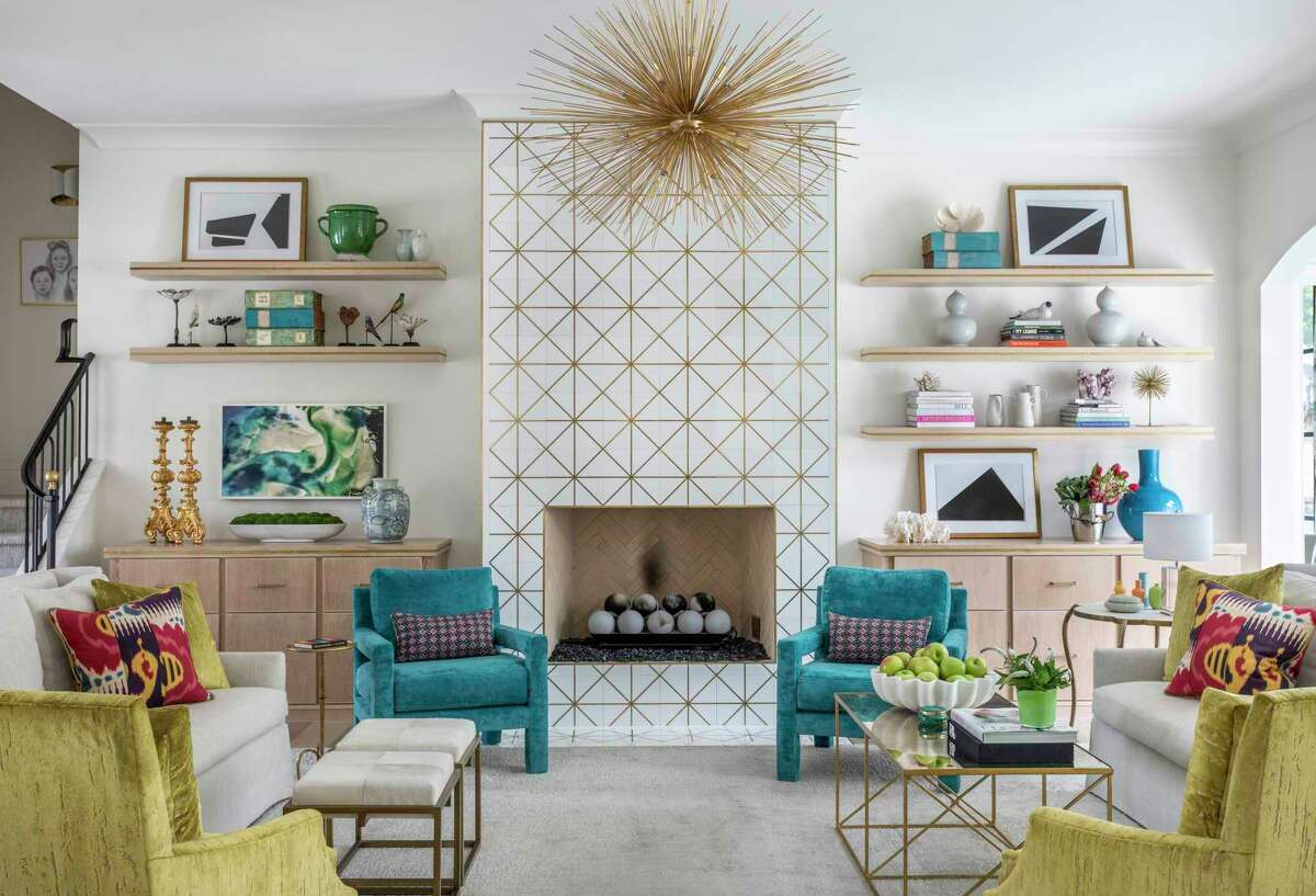 White marble tile with brass inlay creates a feature wall in the living room and is a striking backdrop for the spiky starburst chandelier.