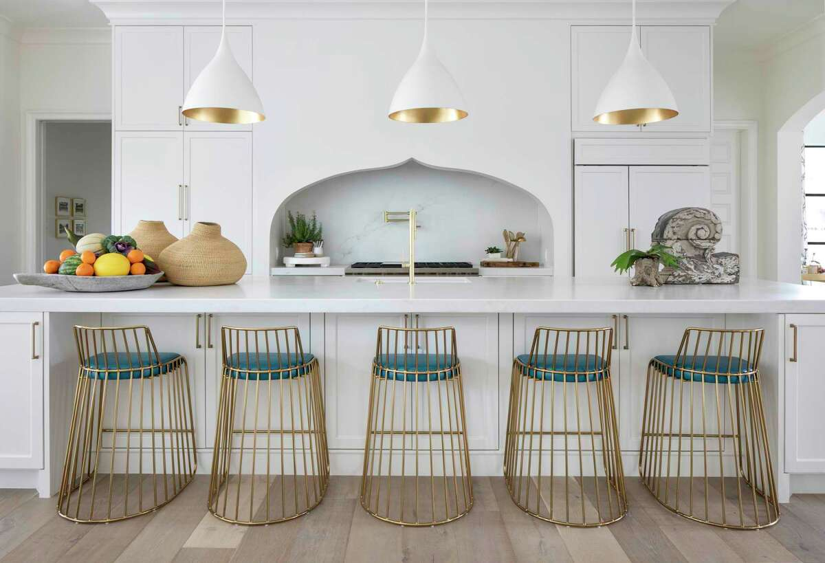 Warm gold appears in lighting, plumbing fixtures and barstools in the kitchen.