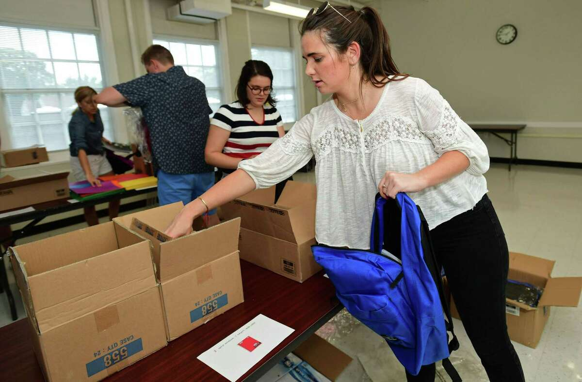 Volunteers from Albourne America, a local alternative investment firm, including Suzanna Hamer fill 80 backpacks with school supplies for children in Family & Children's Agency programs Thursday, August 22, 2019, at the FCA facility at Ben Franklin School in Norwalk, Conn.