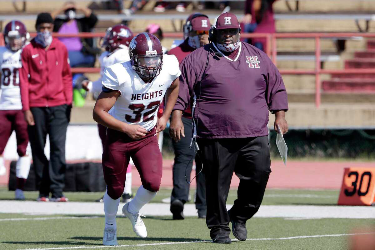 Heights head football coach Stephen Dixon Sr., right, give instructions to player Nathan Alonzo (32) as he enters the field during their their game against Westside at Butler Stadium Saturday, Oct. 31, 2020 in Houston, TX.