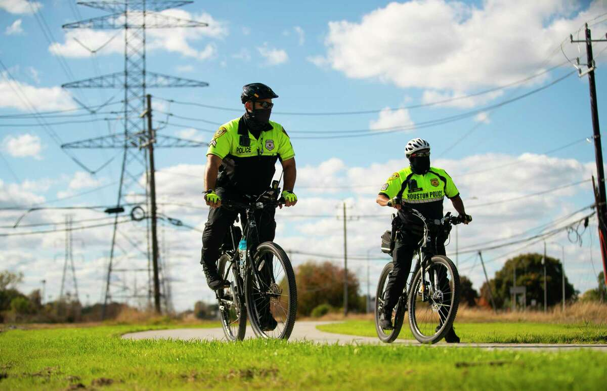 Houston police offers ride the trail before a ribbon-cutting dedication of the first phase of a trail that runs from Wirt Road to Blalock Road in Spring Branch on Dec. 10, 2020, in Houston. Local officials are planning a trail that will extend from Addicks Reservoir to White Oak Bayou when completed.
