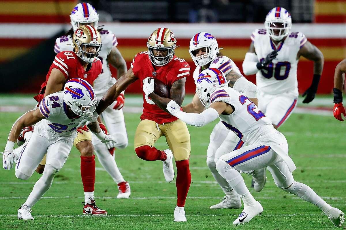 49ers running back Raheem Mostert runs between Bills defensive backs Taron Johnson and Micah Hyde on Monday.