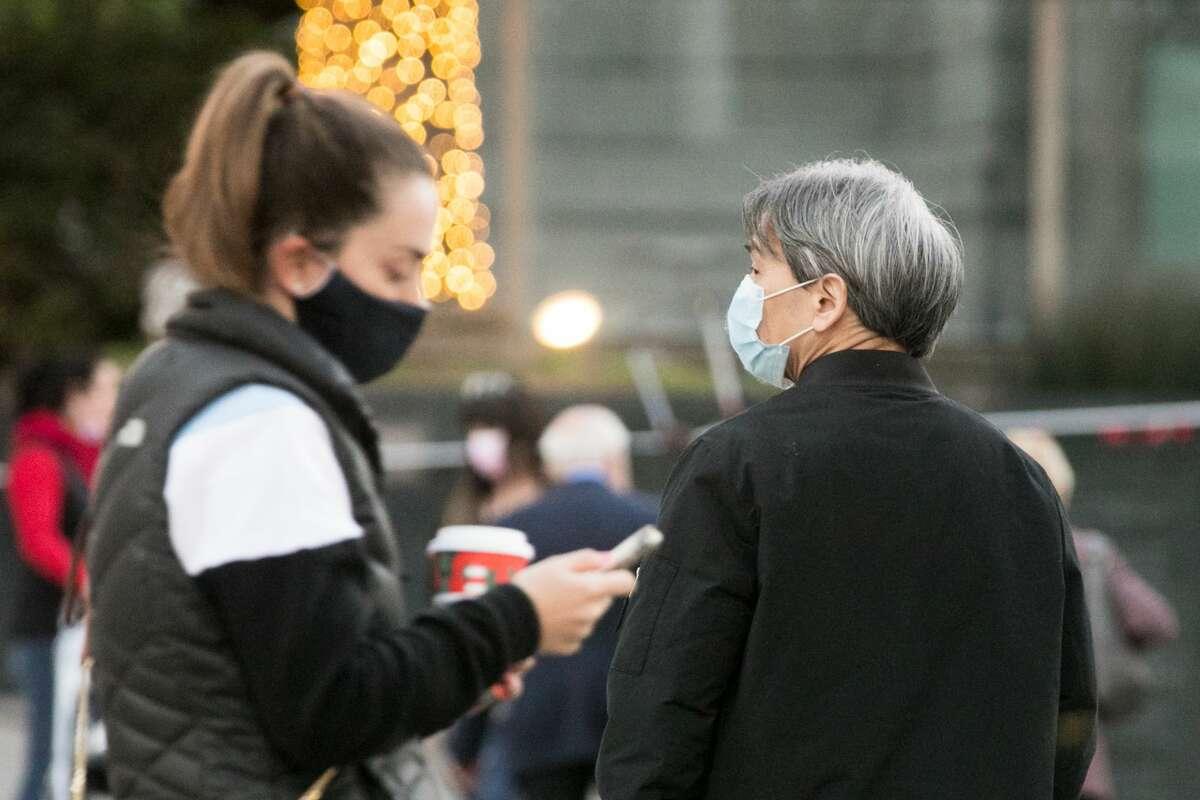 Pedestrians wearing masks walk through Union Square in San Francisco, California on Dec. 8, 2020.