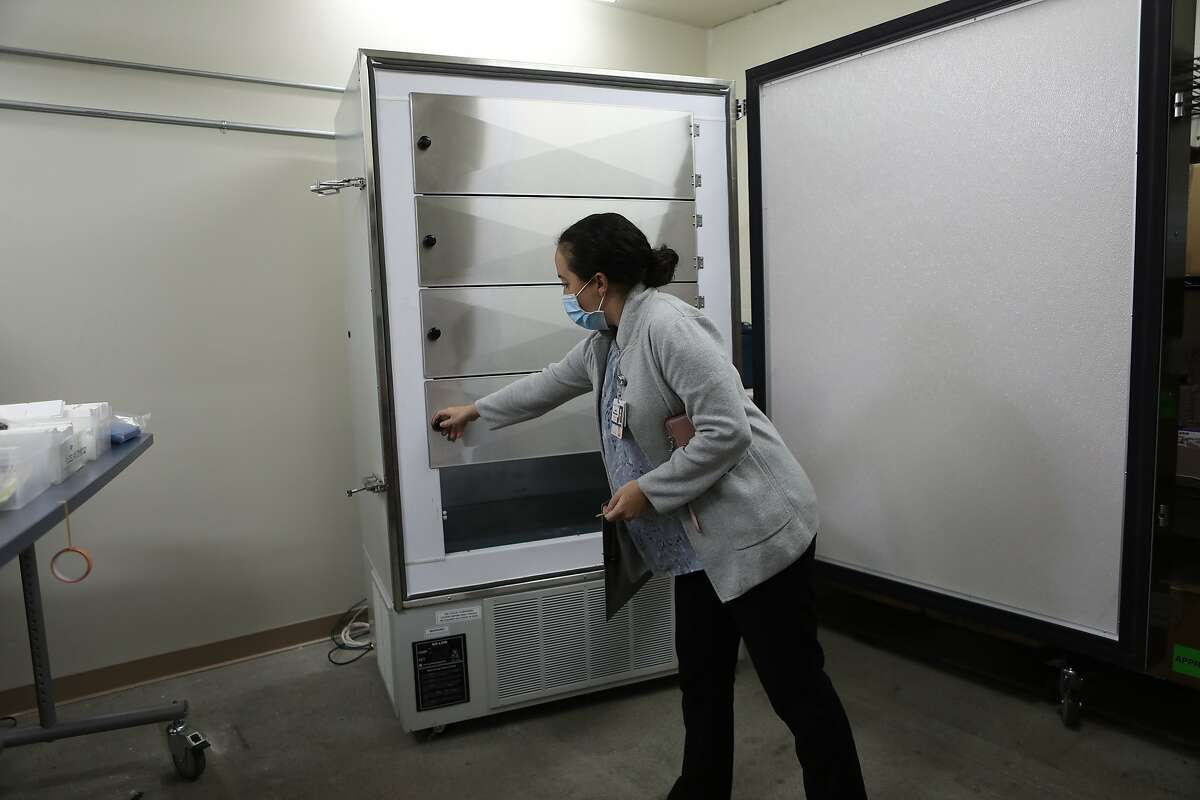 Leigh Witherspoon, clinical pharmacist at Santa Rosa Memorial Hospital, opens a freezer that can hold 250,000 doses of the COVID-19 vaccine in small vials.