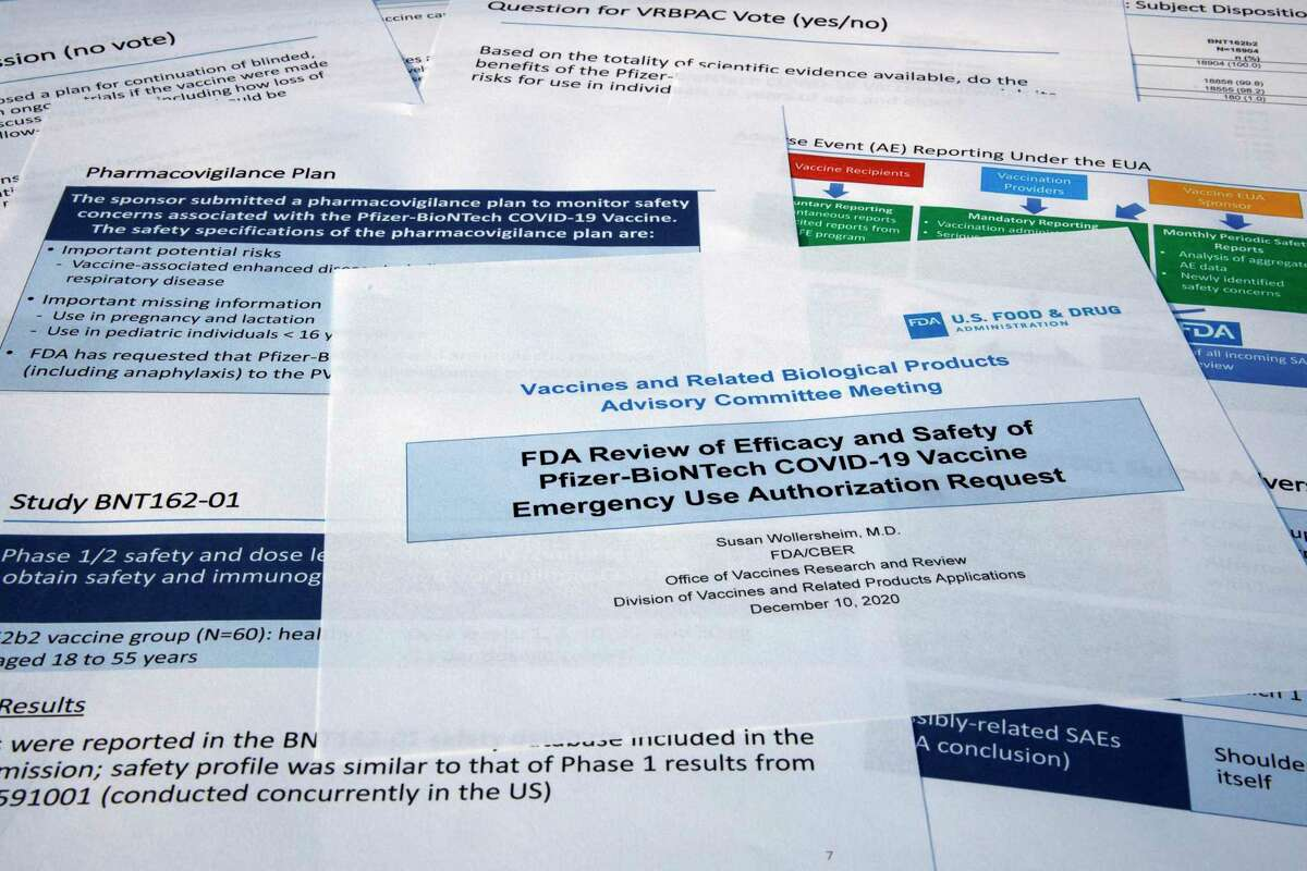 Documents created by the Food and Drug Administration for the meeting with the FDA advisory panel, as Pfizer seeks approval for emergency use of their COVID-19 vaccine, are seen on Thursday, Dec. 10, 2020. The FDA panel functions like a science court. During the scheduled daylong session, it was expected to debate and pick apart the data on whether the vaccine is safe and effective enough to be cleared for emergency use. (AP Photo/Jon Elswick)