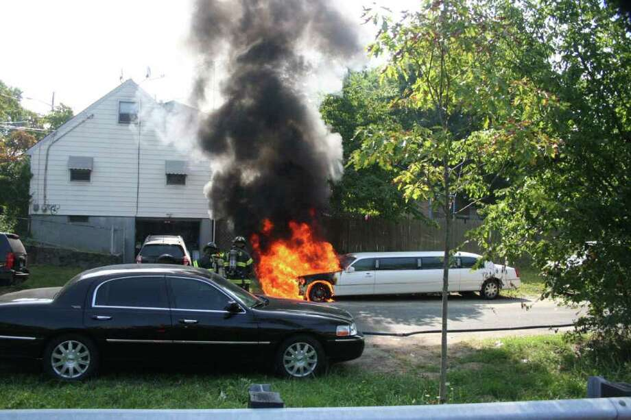 Flames eruupt in the engine compartment of a stretch limousine off Kings Highway, at New Hampshire Avenue, on Friday morning. The $50,000 vehicle was a total loss, according to fire officials. Photo: Contributed Photo / Fairfield Citizen contributed