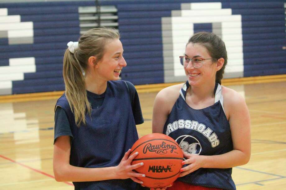 Crossroads' Amelia Thompson and Allison Thompson share some comments after a practice in early November. (Pioneer photo/John Raffel)