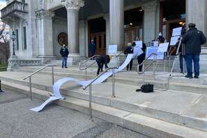 School based labor union representatives make a point at the Connecticut State Capitol on Thursday, rolling out a 20 foot scroll representing 14,000 signatures they collected asking schools be closed until more pandemic safeguards are in place.
