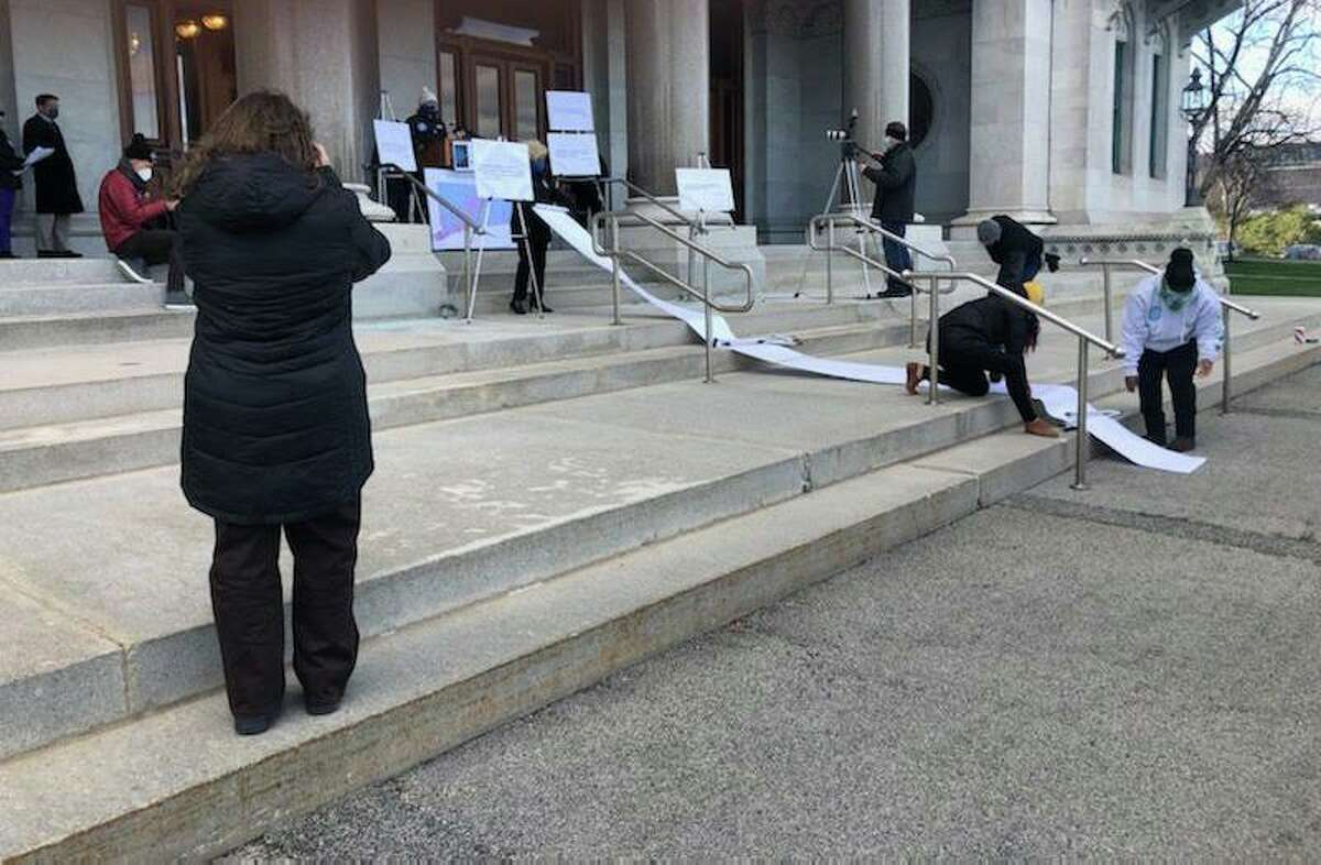 School based labor union representatives make a point at the Connecticut State Capitol on Thursday, rolling out a 20-foot scroll representing 14,000 signatures they collected asking schools be closed until more pandemic safeguards are in place.