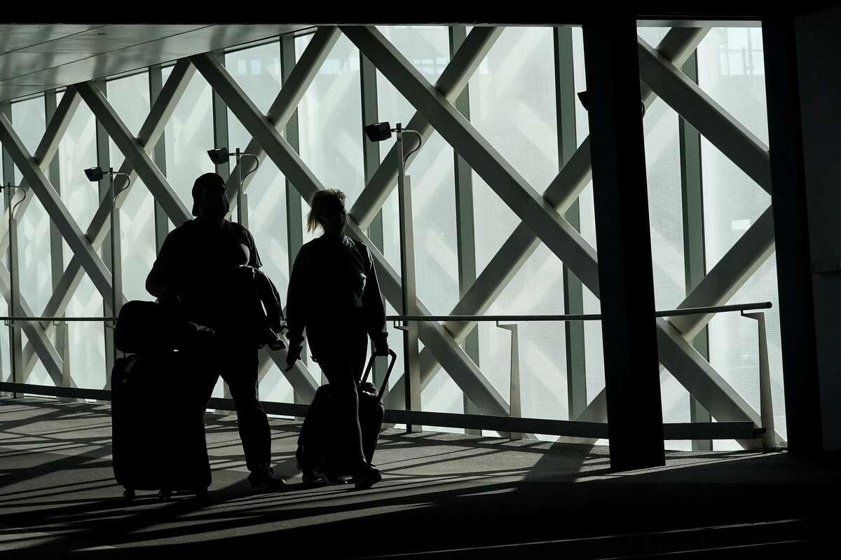 Travelers walk toward terminals at San Francisco International Airport during the coronavirus outbreak in San Francisco, Tuesday, Nov. 24, 2020.