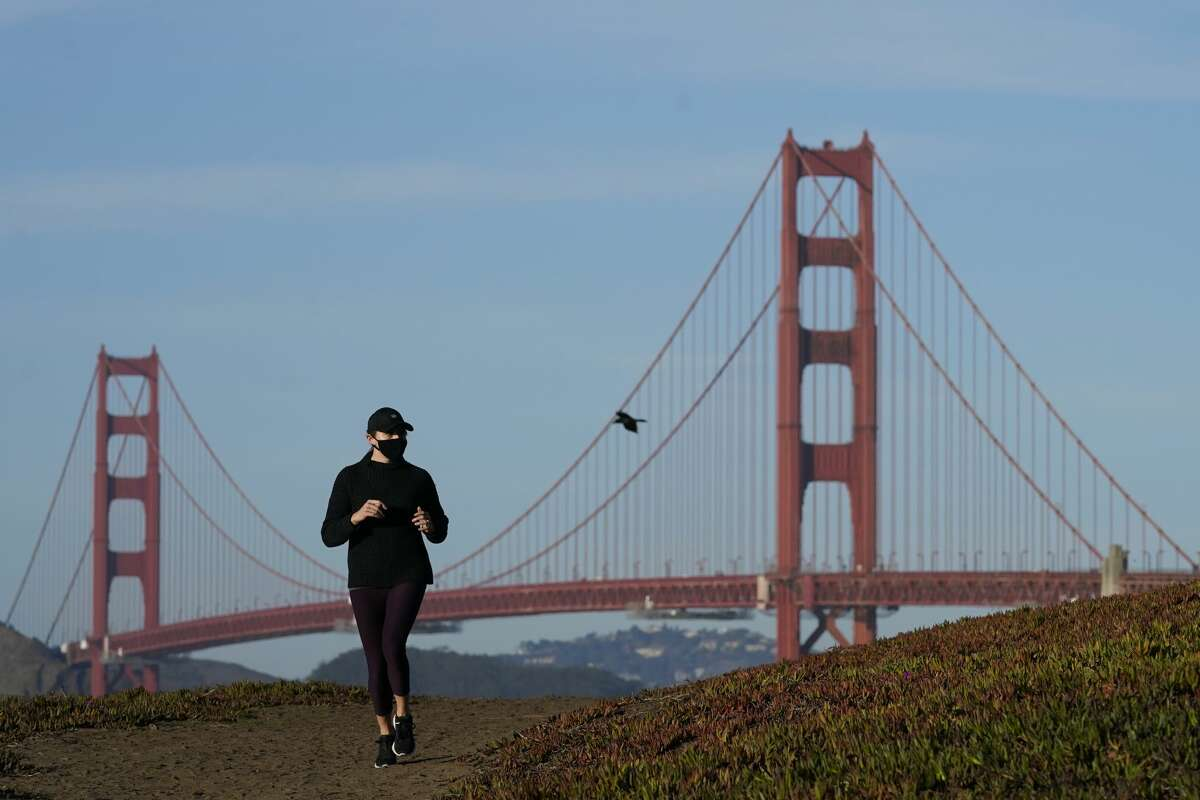 A person wearing a mask runs on a path in front of the Golden Gate Bridge during the coronavirus pandemic in San Francisco, Monday, Nov. 30, 2020.