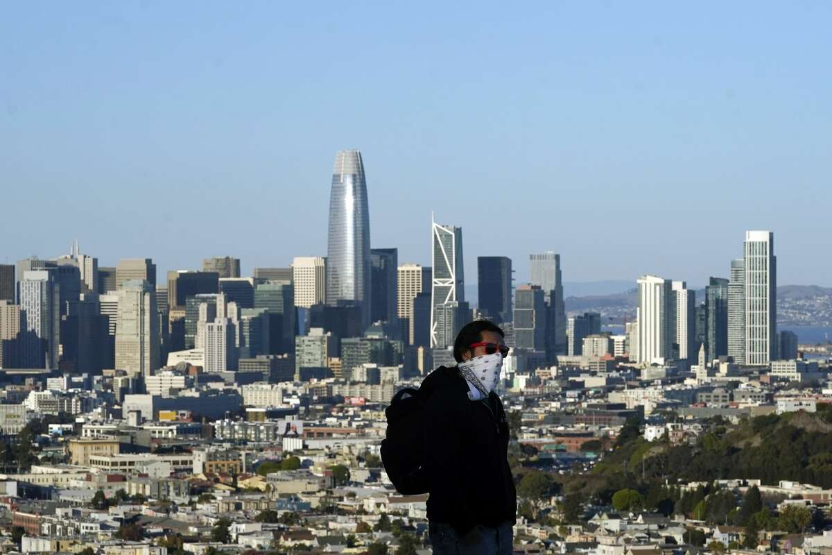 A person wearing a protective mask walks in front of the skyline on Bernal Heights Hill amid the coronavirus pandemic in San Francisco, Monday, Dec. 7, 2020.