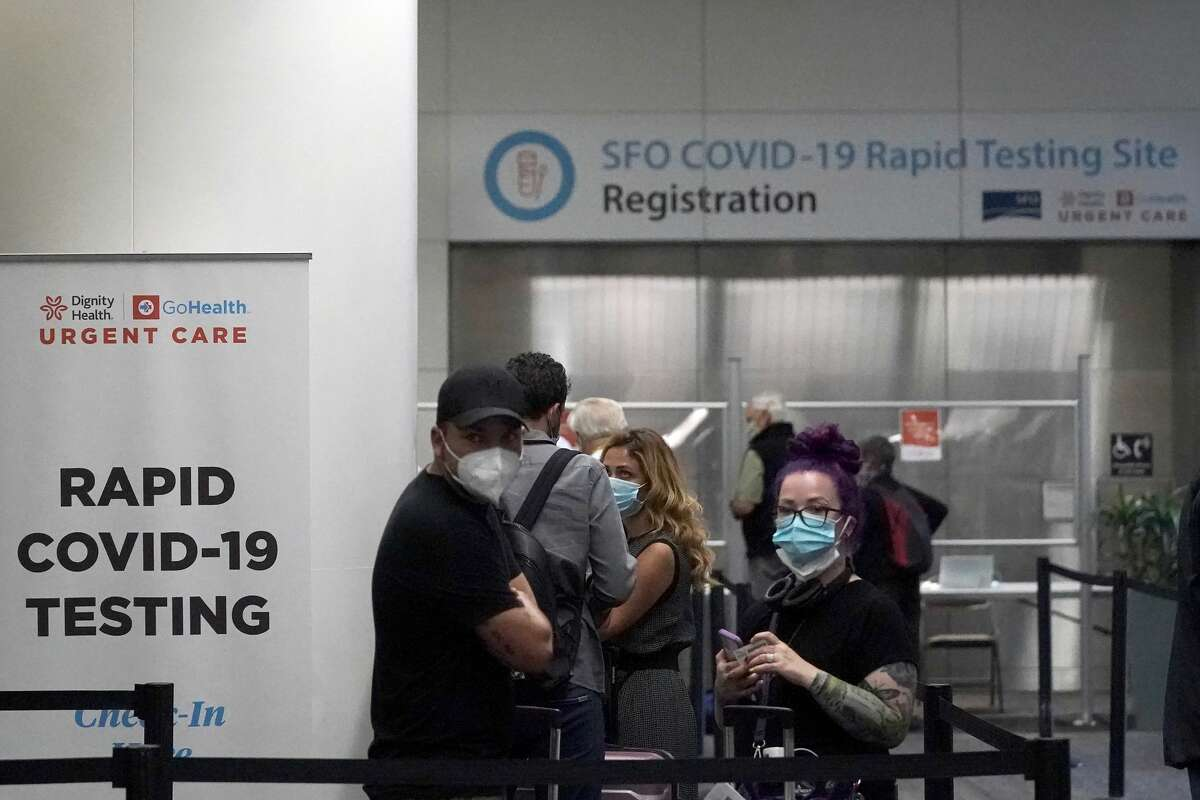 In this Oct. 15, 2020, file photo, United Airlines passengers wait in line to register at the SFO COVID-19 rapid testing site at San Francisco International Airport in San Francisco.