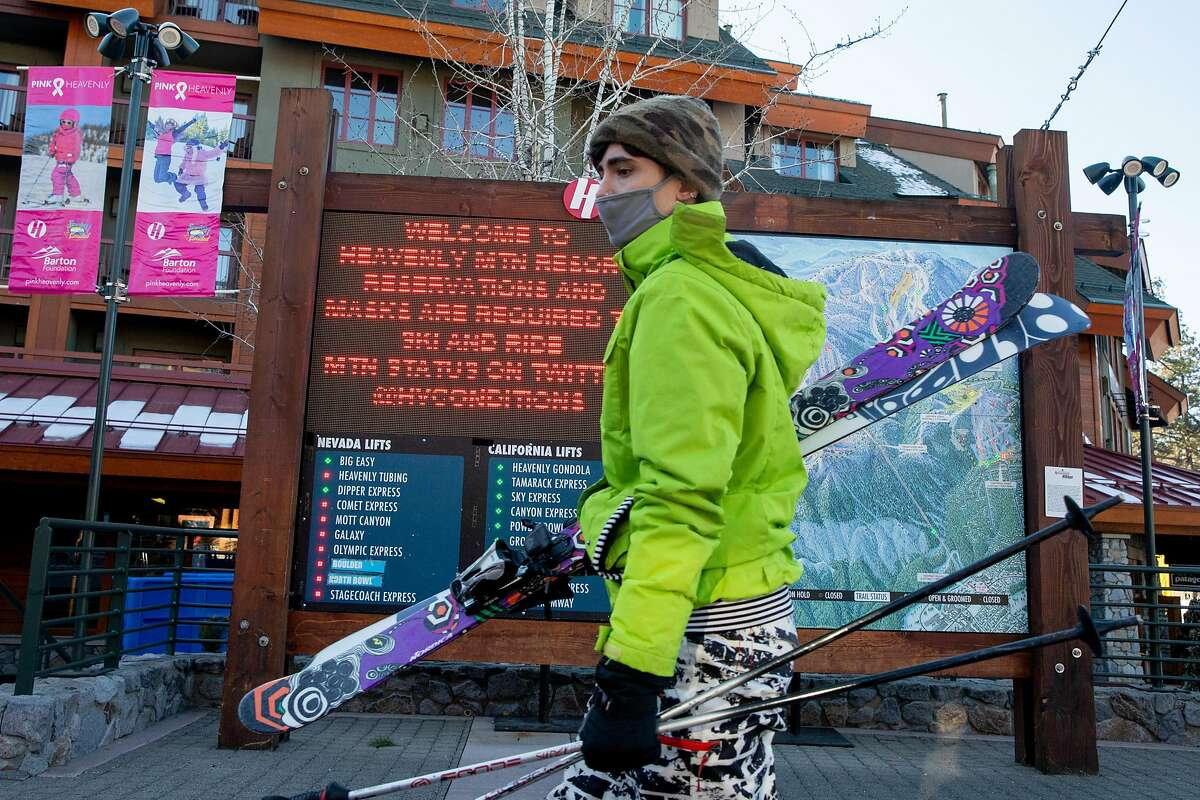 A masked skier makes their way to the Heavenly Mountain gondola at Heavenly Village in South Lake Tahoe, Calif. Thursday, December 10, 2020. Vacation travel to Lake Tahoe will be banned for at least three weeks starting Friday due to a regional rise in the number of COVID-19 hospitalizations.