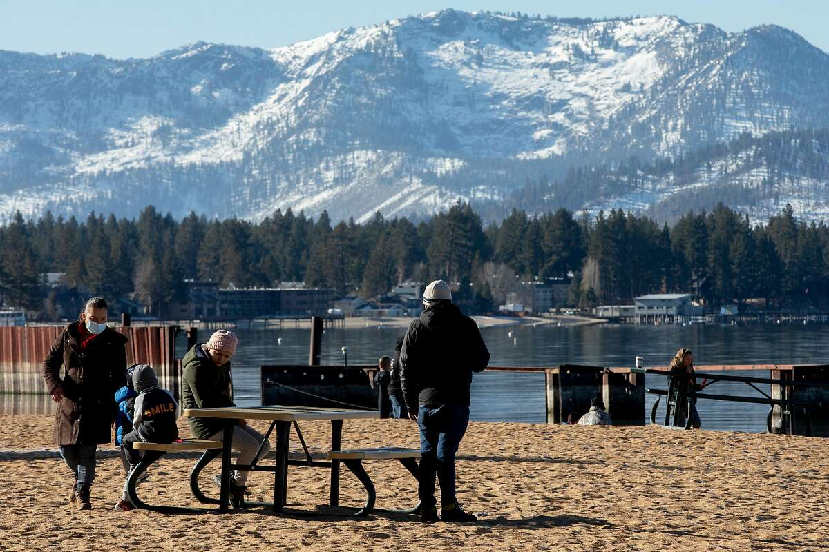 A family enjoys Lakeside Beach in South Lake Tahoe ahead of the travel ban that will be imposed on the region.
