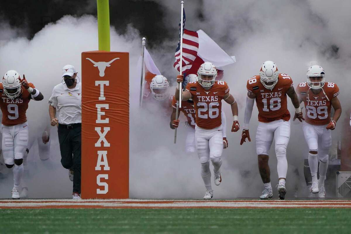 Texas head coach Tom Herman, second from left, and his players run onto the field for an NCAA college football game against Iowa State, Friday, Nov. 27, 2020, in Austin, Texas. (AP Photo/Eric Gay)