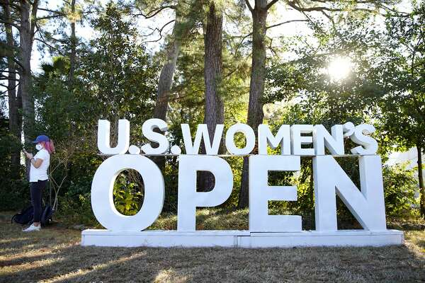 A woman stands near the backdrop for the U.S. Women's Open in Houston on Thursday, Dec. 10, 2020.