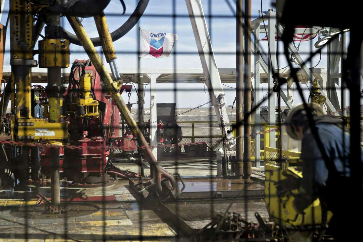 A Chevron Corp. flag flies on the drilling floor of a Nabors Industries Ltd. drill rig in the Permian Basin near Midland, Texas, U.S., on Thursday, March 1, 2018.