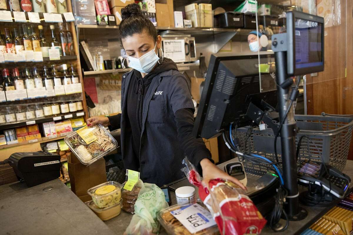 """Melissa Lopez wears a mask while working the checkout counter at Bi-Rite Market in the Mission District of San Francisco. Who gets a vaccine first in many ways it will come down to how state health departments define """"essential workers."""""""