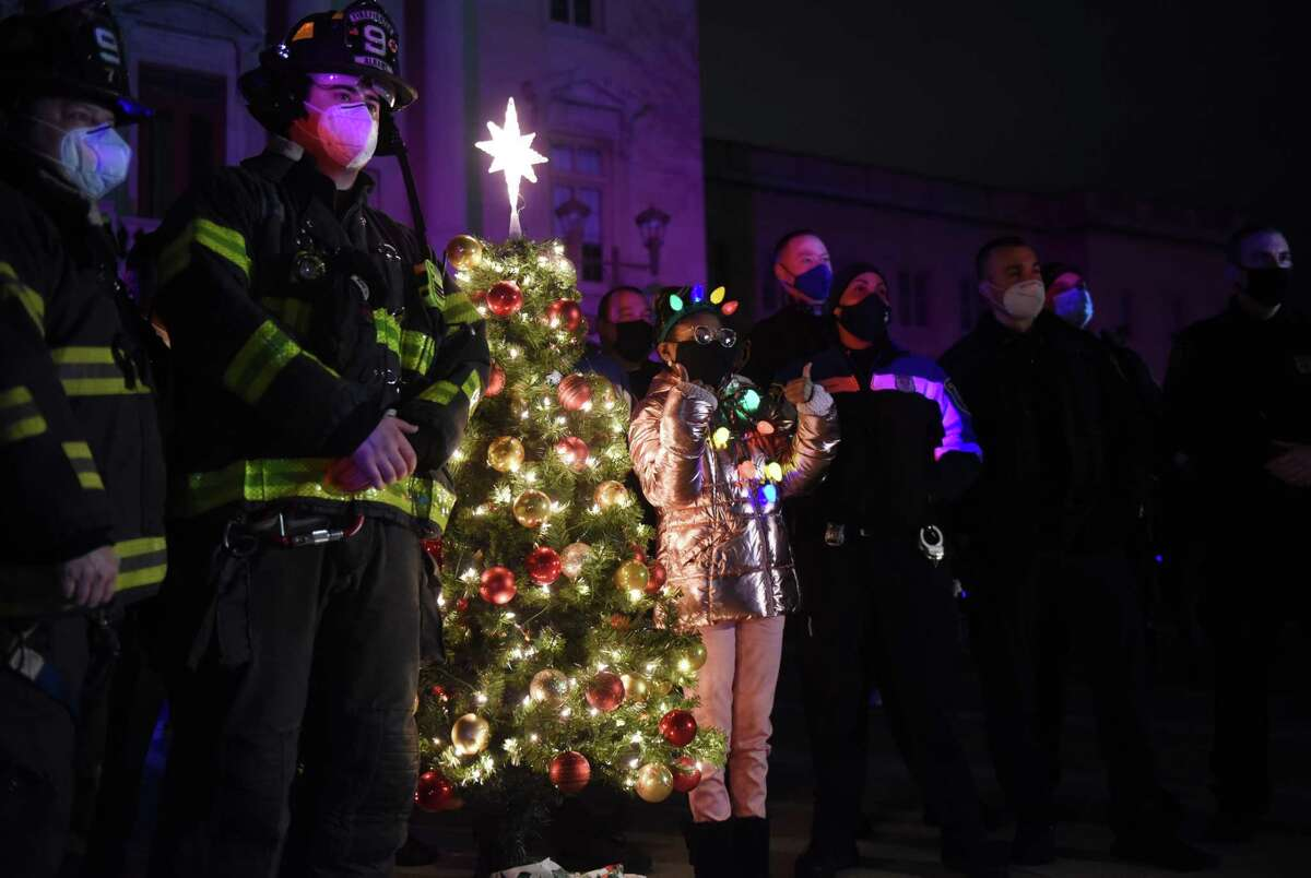Maliha Jackson, 14, poses with members of the Albany fire and police departments during a surprise tree lighting ceremony held for her on Thursday, Dec. 10, 2020, at Hackett Middle School in Albany, N.Y. (Will Waldron/Times Union)