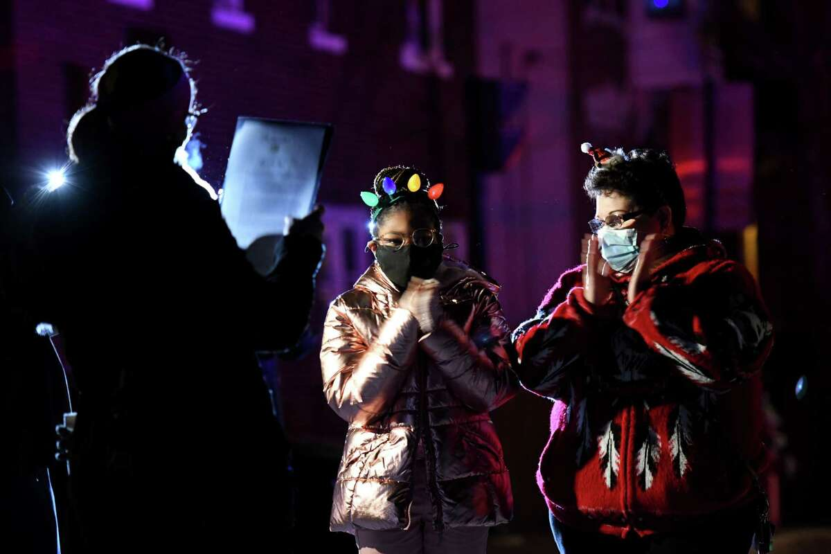 Maliha Jackson, 14, center, has a proclamation from the City of Albany read to her during a surprise tree lighting ceremony with her mother, Aqilah Jackson, right,on Thursday, Dec. 10, 2020, at Hackett Middle School in Albany, N.Y. (Will Waldron/Times Union)