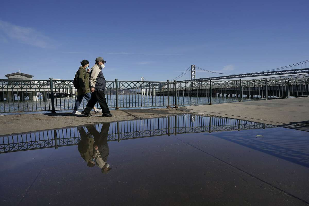 People walk on San Francisco's Embarcadero past evidence of the king tide on Nov. 16, 2020.