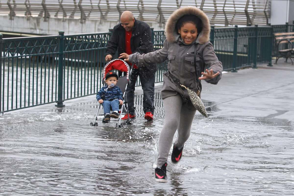 Araya Villareal dashes through water spilling onto the sidewalk with her father Isaac pushing his nephew Jamison McCall in a stroller at Pier 14 along the Embarcadero during a 2015 king tide.