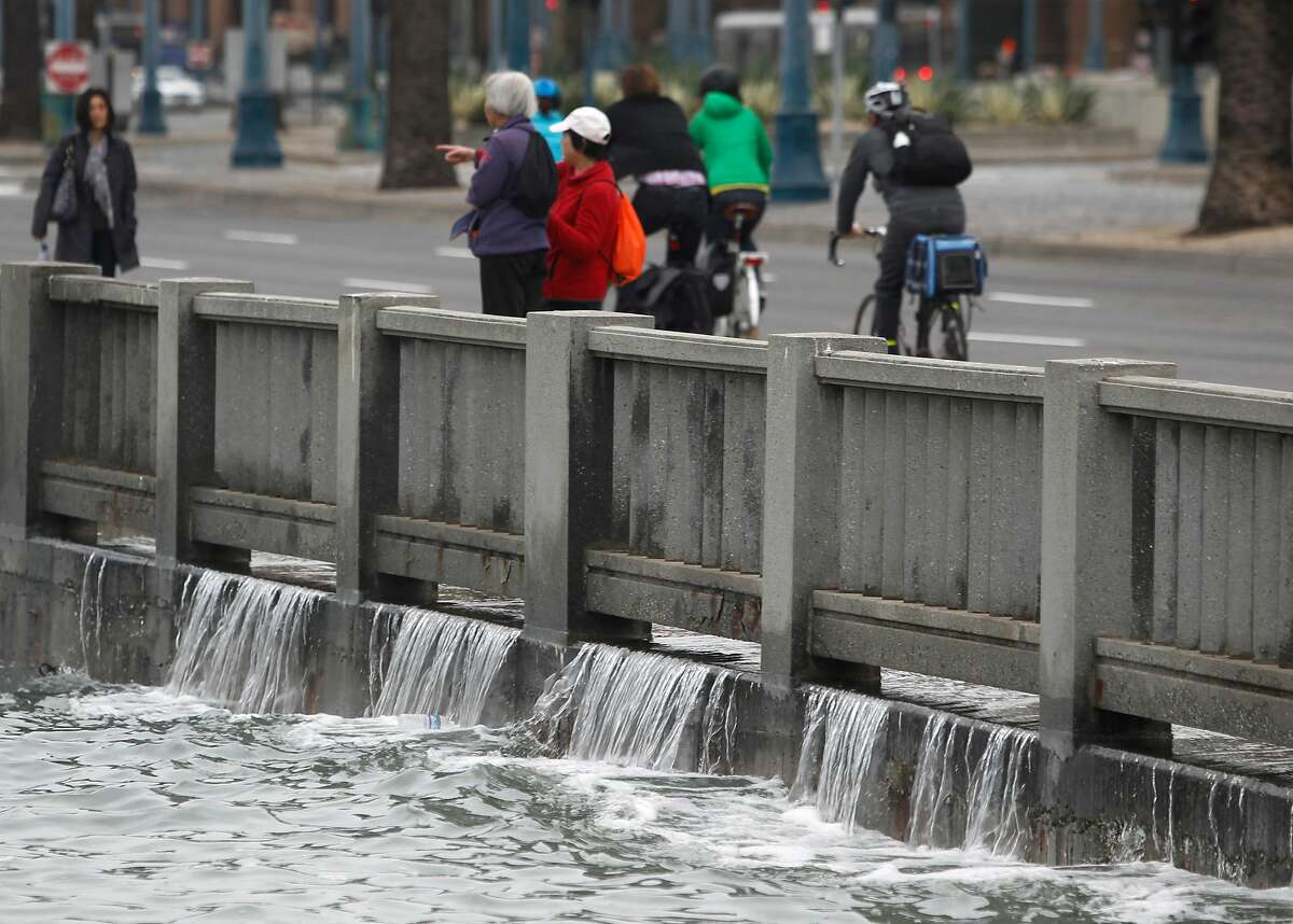 Pedestrians on the Embarcadero watch water recede from the sidewalk at Pier 14 during a high tide in 2015.