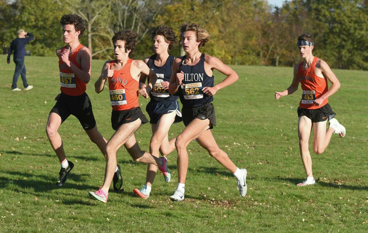 Runners Charlie King (457), Chuckie Namiot (460) and Liam Carcich (453) of Ridgefield, Davis Cote (562) of Wilton, and Dillon Harding (502) of Staples race along the course in New Canaan's Waveny Park during the FCIAC East boys cross country championship on Nov. 4.