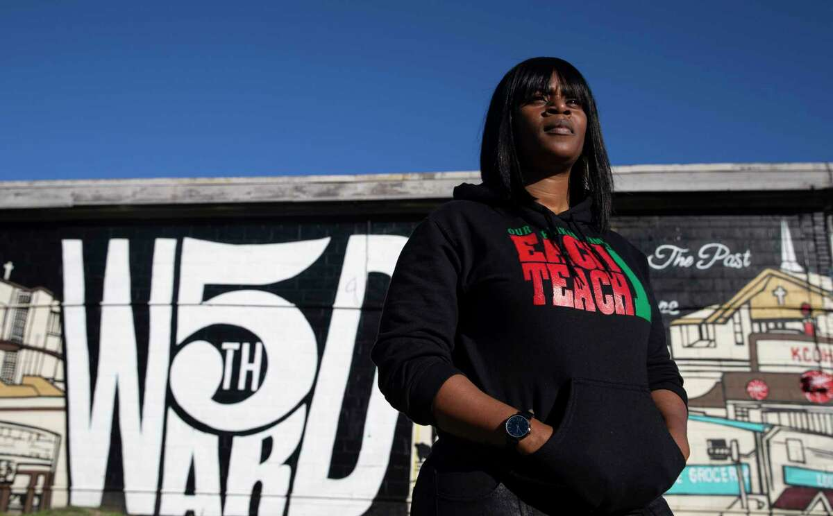 Kendra London poses for a photograph against a mural of Fifth Ward landmarks Wednesday, Dec. 9, 2020, at Fifth Ward in Houston. A city agency supports a huge development proposed along south of Clinton Drive between Jensen Drive and Hirsch Road. Community activists, including London, whose family have been living in the neighborhood for six generations, worry the development will drive out existing low-income residents in the historical Black neighborhood.
