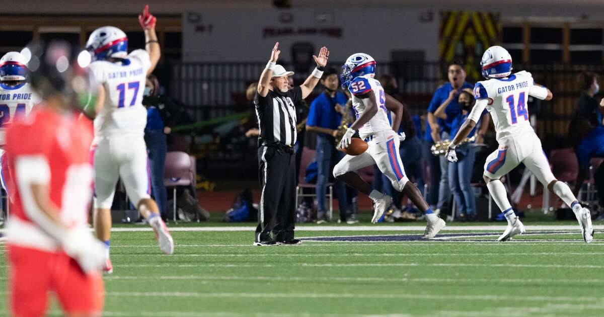 Jonathan Pruyn (52) of the Dickinson Gators intercepts a Dawson Eagles pass and returns it for a touchdown in the first half during a High School bi-district playoff football game on Thursday, December 10, 2020 at Pearland ISD Stadium in Pearland, Texas.