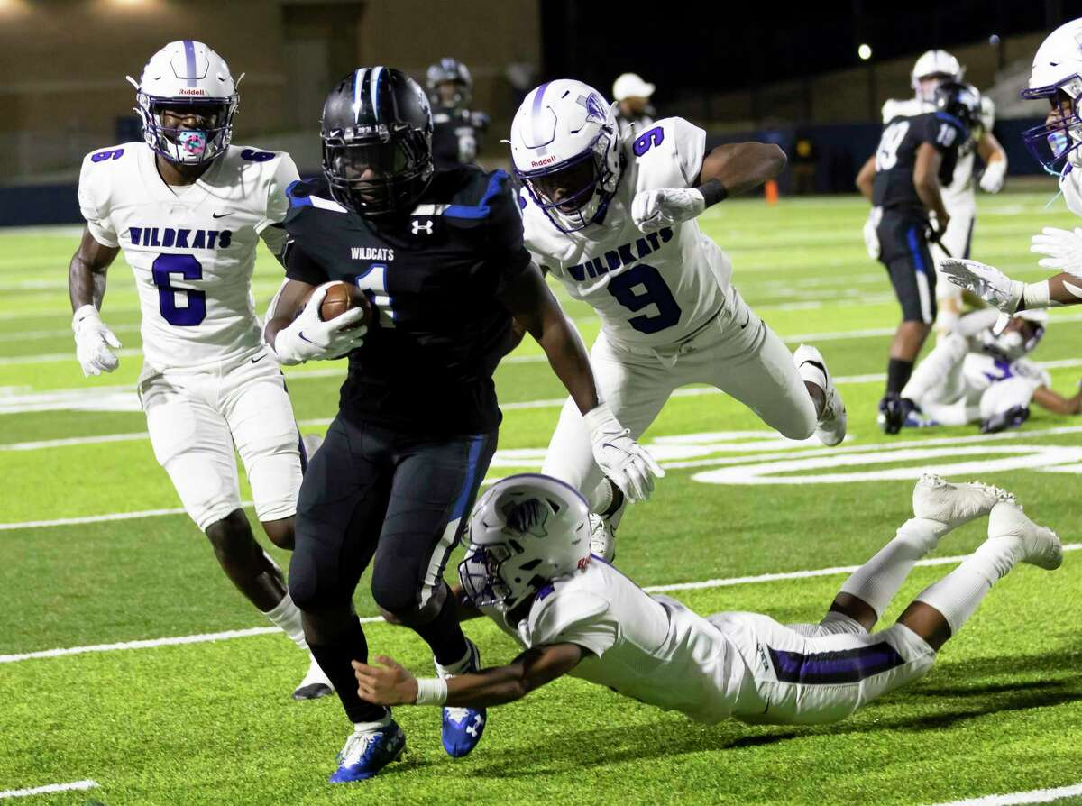 Dekaney running back Lamont Lawrence (1) is tackled by Willis athlete Tallas Harrison (9), linebacker Trevor Jones (6) and defensive back Devon Lovelady (4) during the second quarter of a Region II-6A (Div. II) bi-district football game at Planet Ford Stadium in Spring.