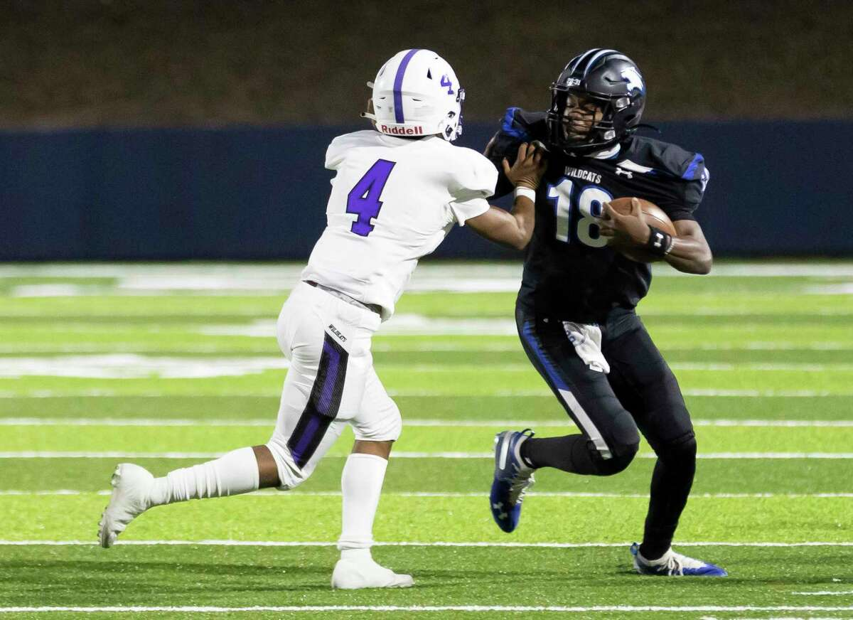 Dekaney quarterback Daelyn Williams (18) is corralled out of bounds by Willis defensive back Devon Lovelady (4) during the first quarter of a Region II-6A (Div. II) bi-district football game at Planet Ford Stadium in Spring.