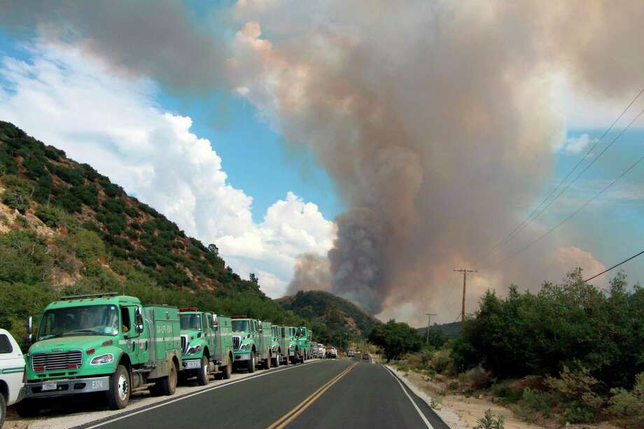 Support vehicles parked along Pine Canyon Road, north of Los Angeles, California, while the Lake Fire is visible in the background. (Judy Nathan/U.S. Forest Service Photo)