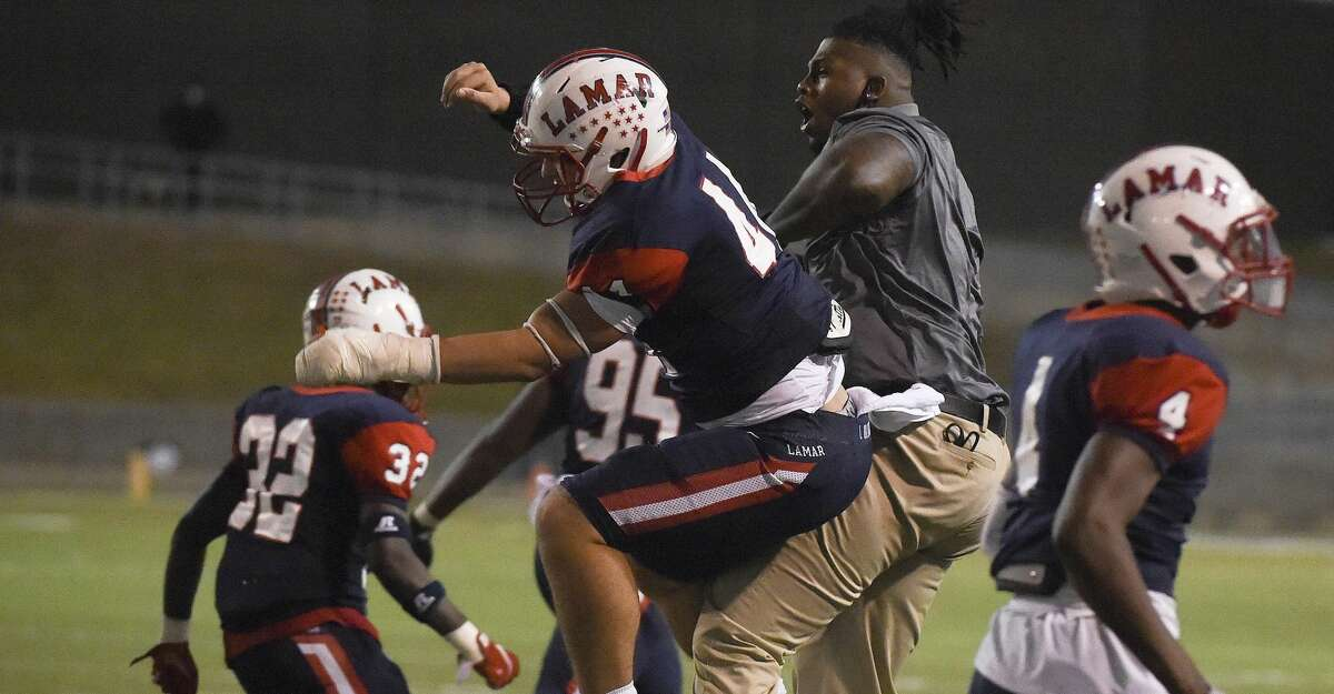 Lamar linebacker Santiago Gomez, center, celebrates a safety with a coach during the second half of a 6A Division II Region III bi-district high school football playoff game against Memorial, Thursday, Dec. 10, 2020, in Houston.