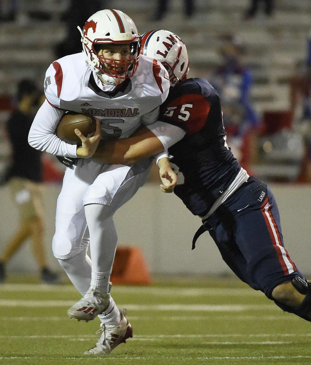 Memorial quarterback Ian Stinneford (5) is sacked by Lamar defensive lineman Max Shilstone during the first half of a 6A Division II Region III bi-district high school football playoff game, Thursday, Dec. 10, 2020, in Houston.