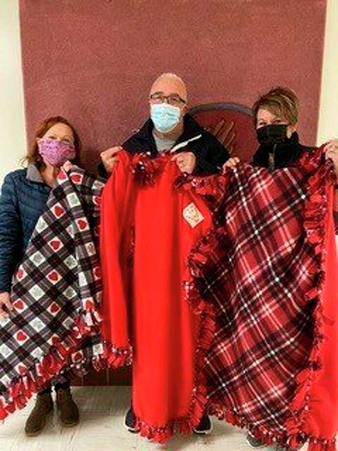Midland Community Former Offenders Advocacy's executive director Rob Worsley, middle, accepts fleece blankets made by the Ladies of Blessed Sacrament recently made and donated fleece blankets for his organization. (Photo provided)