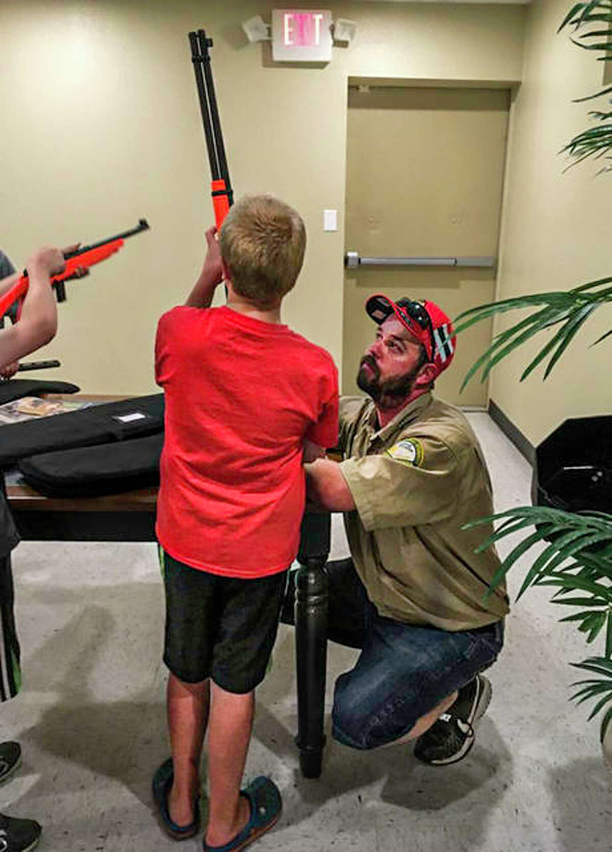 An instructor works with a youngster during an in-person hunting safety course provided by the Illinois Department of Natural Resouces prior to COVID-19.