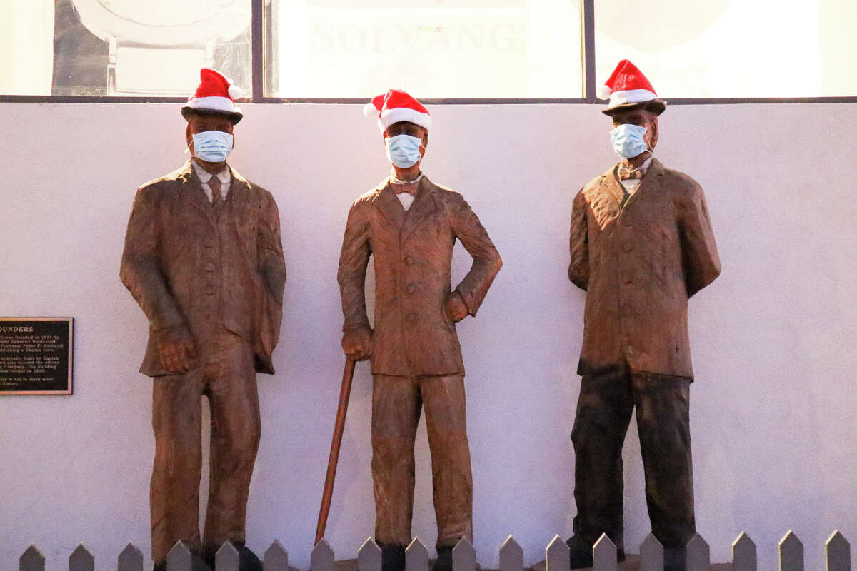 A statue of Solvang's founders has masks and Santa hats for this year's Julefest