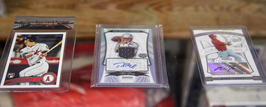 Among highly prized cards found at The Old Ballpark card shop in Alvin are, from left, a 2011 Topps Mike Trout rookie card, as well as autographed cards of Tom Brady and Trout. Photo: Jon Shapley, Staff Photographer / Staff Photographer / © 2020 Houston Chronicle