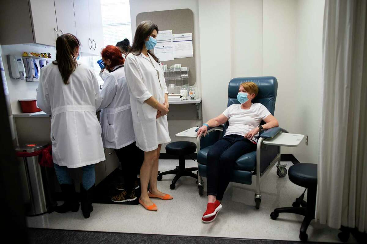 Hana El Sahly, center, an associate professor of molecular virology and microbiology and infectious diseases at Baylor College of Medicine talks to Linda Lamberth, right, 66, an experimental vaccine trial volunteer before getting injected with the vaccine on Friday, Aug. 7, 2020, in Houston.