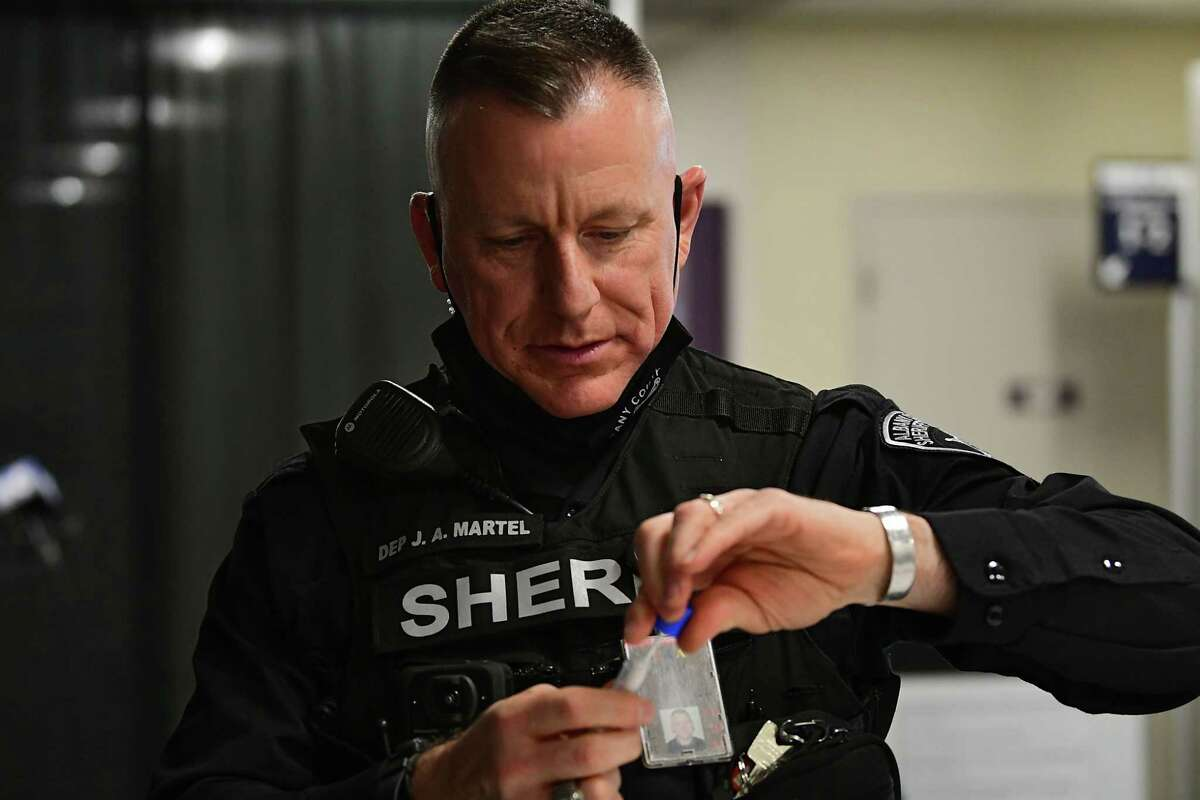 Deputy Sheriff Joseph Martel secures his sample in a test tube as he takes a SUNY-developed saliva test which airport employees began taking at Albany International Airport on Friday, Dec. 11, 2020 in Colonie, N.Y. The plan is to eventually open testing to the public. (Lori Van Buren/Times Union)