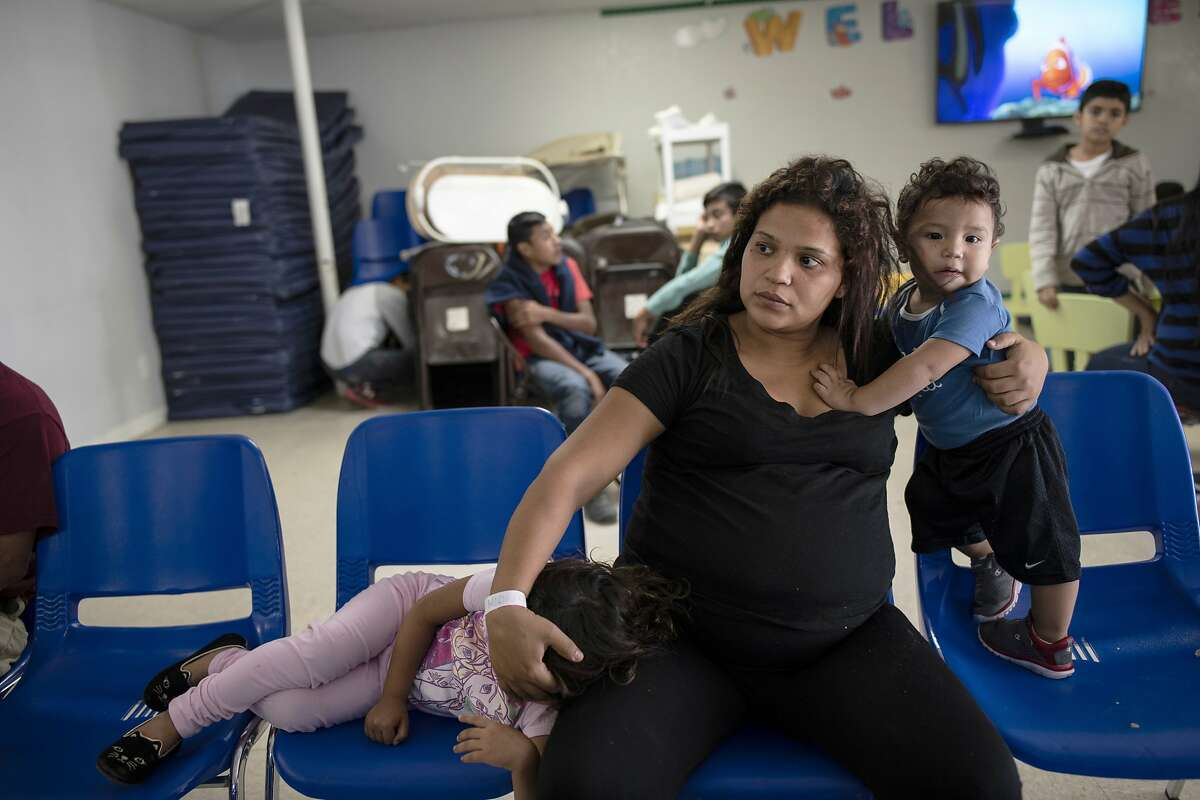 Xiomara Quintanilla a mother who fled El Salvador with her children, Brianna, 3, and Dylan, 1, sits with them several days after crossing the Rio Grande River and seeking asylum in the United States near McAllen, Texas, in 2018.