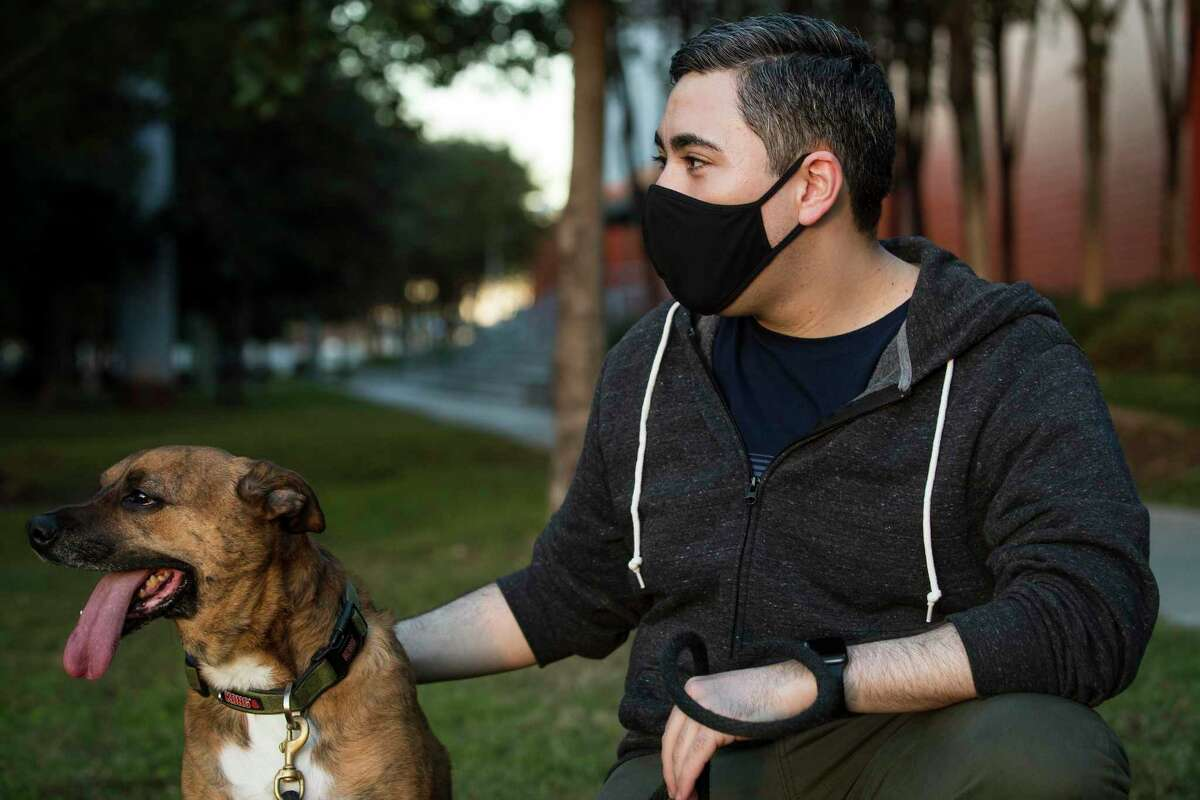 Ruben Cardona poses for a portrait with his dog, Ramsey, outside his apartment on Tuesday, Dec. 8, 2020 in Houston. Cardona used to struggle taking his dogs for a walk due to his weight, about 5 months ago, he had a gastric bypass surgery and has dropped 80 pounds. he said now he can go for longer walks with no problem and the dogs are appreciative.