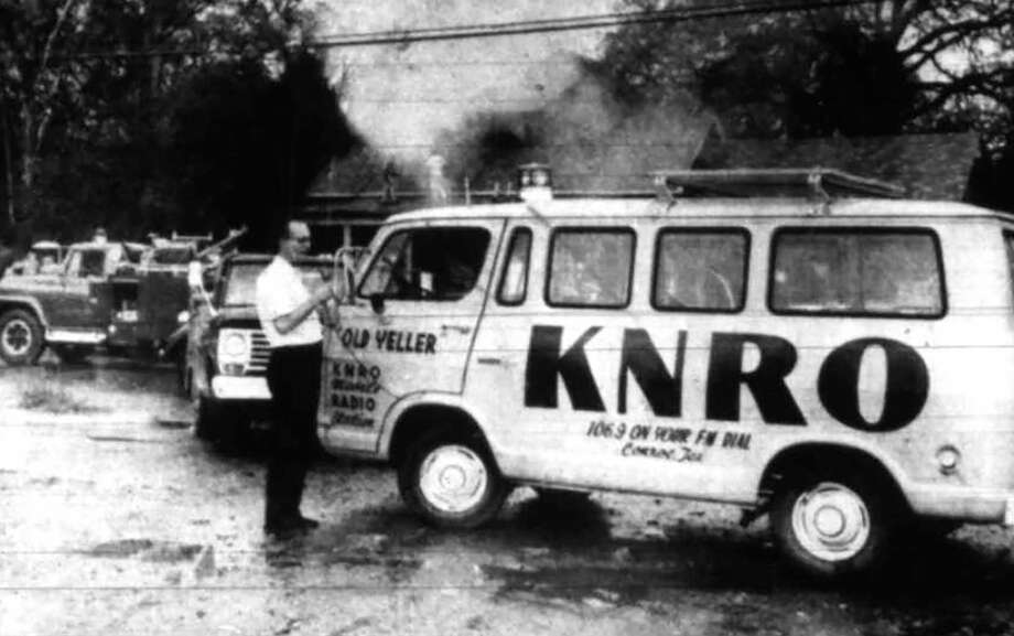 "Ed Watson and the news van ""Old Yeller"" on the scene of a house fire in Conroe. Watson was the news director for KNRO FM radio station in Conroe. He also worked for The Courier for several decades. Photo: Courier File Photo"