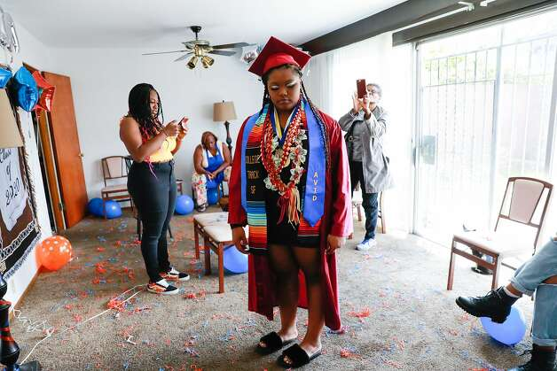 Ja�el Bryant, 17 (center) stands as her family and friends photograph her cap and gown during her graduation party on Saturday, June 20, 2020 in San Francisco, California. After many weeks of debating Ja�el accepted a spot at Virginia State University where she will be starting in the fall. The school has decided to only let freshman and seniors attend school in person so that they can house the students the students in single rooms due to the coronavirus. Ja�el said she�s �sad� not to have a roommate as that was something she�s been looking forward to. Photo: Gabrielle Lurie, The Chronicle