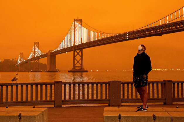 Eli Harik of San Francisco wears a mask while looking up at the dark orange sky hanging over the Embarcadero in downtown San Francisco, Calif. Wednesday, September 9, 2020 due to multiple wildfires burning across California and Oregon. Photo: Jessica Christian, The Chronicle